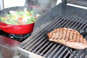 Gmuesepfanne auf Seitenbrenner und Flank Steak auf Grillrost - die frau am grill