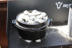 Dutch Oven-Briketts-Die Frau am Grill