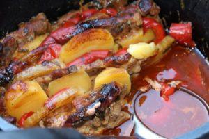 Fleisch, Kartoffel, Paprika und Soße im Dutch Oven-Die Frau am Grill
