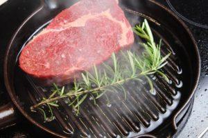 Fleisch anbraten-Gusspfanne-die frau am grill-web