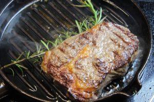 Fleisch wenden-Gusspfanne-die frau am grill-web