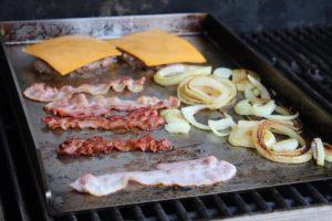 smashed burger mit belag auf feuerplatte - die frau am grill