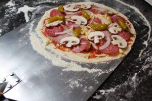ungebackene pizza auf pizzaheber - die frau am grill